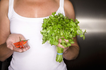 Close up of woman holding peppers and cilantro