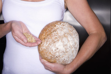 Close up of woman holding fresh bread and grains