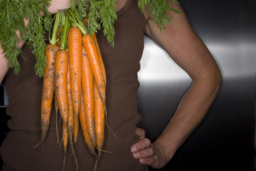 Close up of woman holding fresh carrots