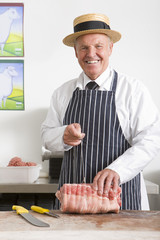 Butcher in uniform preparing roast