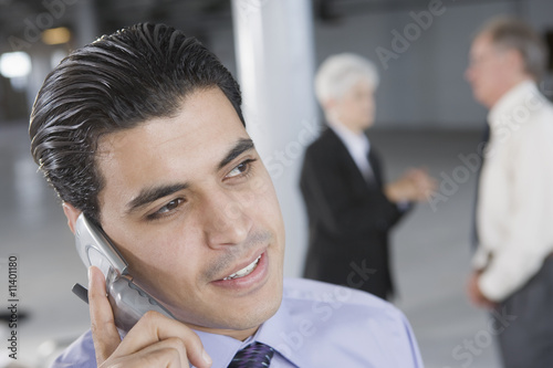 Businessman on a cell phone and colleagues in the background