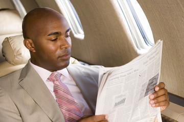 Businessman reading newspaper on aeroplane, close-up
