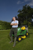 Senior man leaning on riding lawn mower