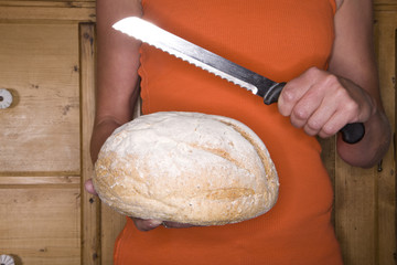 Close up of woman holding loaf of bread and serrated knife