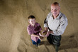 Farmer and grandson holding wheat grains
