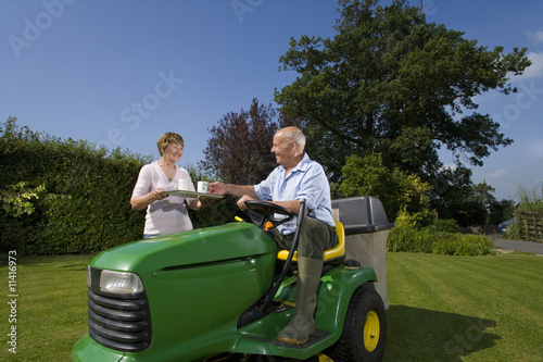 Woman bringing coffee to husband on riding lawn mower