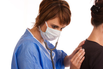 Female doctor examining a patient using a stethoscope