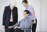 Two women and businessman in a wheelchair