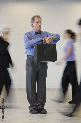 Businessman holding briefcase in busy office