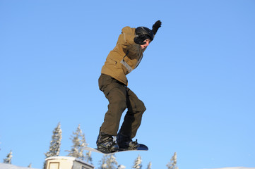 Photo of a young male snowboarder jumping against a blue sky