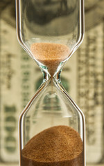 Time - money; hourglass on the background money.