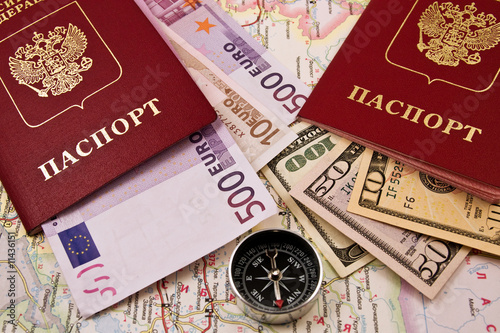 Compass and two passport with the money on a map of Russia
