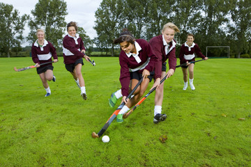Teenage girls playing field hockey