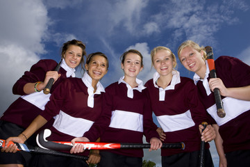 Portrait of smiling teenage girls holding field hockey sticks