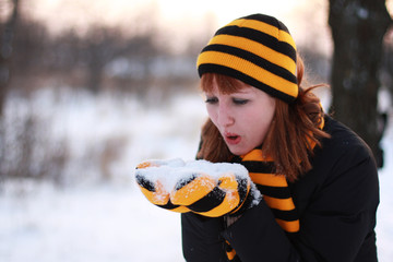 Girl holding snow and blowing on it