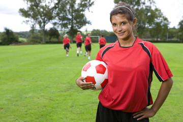 Portrait of teenage girl in uniform holding soccer ball