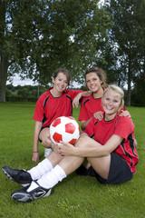 Portrait of smiling teenage girls in soccer uniforms