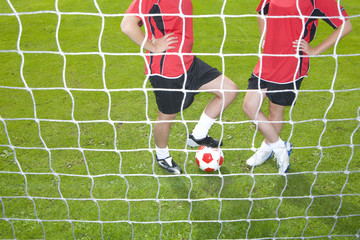 Soccer players with ball standing at goal net