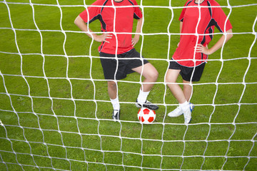 Soccer players standing with ball at goal net