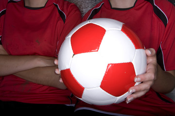 Close up of teenage girls holding soccer ball