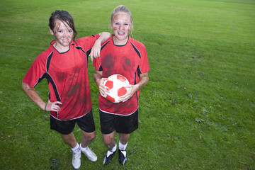 Portrait of muddy teenage girls holding soccer ball on field