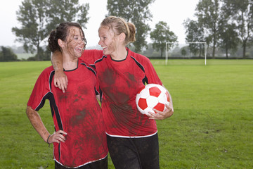 Muddy teenage girls laughing and holding soccer ball on field
