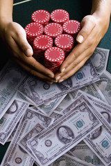 Woman reaching for poker chips on hundred dollar bills