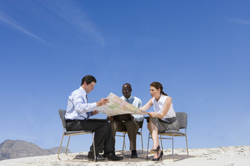 Business people looking at map in remote location
