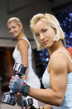 Strong beautiful woman lifting heavy dumbbells