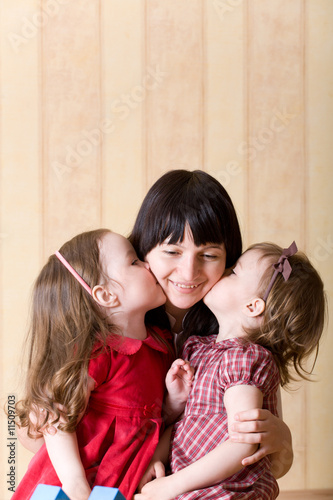 Two little daughter kiss their mother