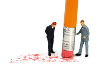 Miniature businessman erases a mistake.Concept.