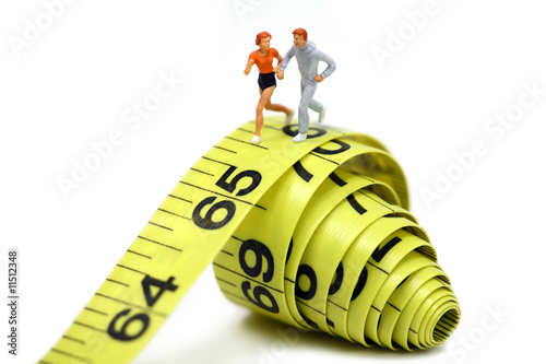 Miniature joggers run on a rolled up yellow measuring tape.