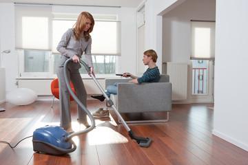 Woman vacuum cleaning man watching tv