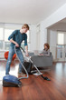 Man vacuum cleaning woman working