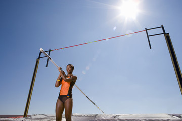 Young female pole vault athlete with pole by bar, low angle view (sun flare)