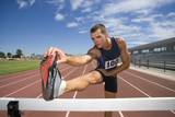 Male athlete stretching hamstrings, foot on hurdle, low angle view
