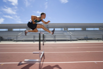 Male athlete jumping over jump (blurred motion)
