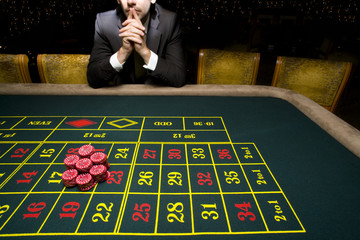 Man gambling at roulette table, mid section