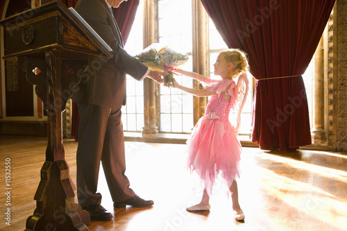 Man by lectern giving flowers to ballerina girl (4-6)
