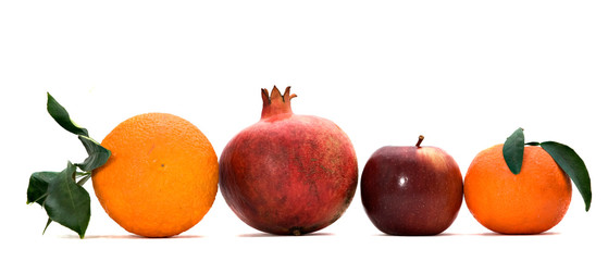 Pomegranate, orange, tangerine, and apple isolated on white back