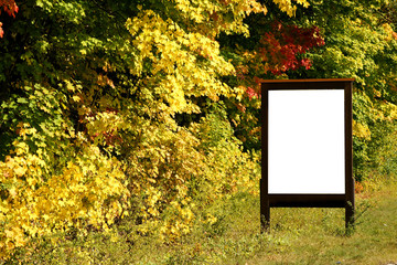 billboard next to autumnly colored trees