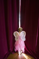 Ballerina girl (4-6) with fairy wings peeking out gap in stage curtains, rear view