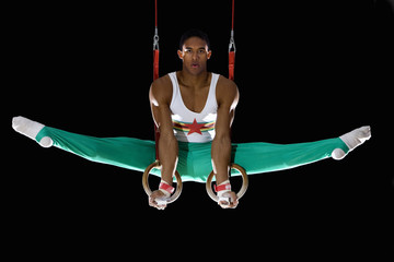 Male gymnast performing on gymnastic rings, portrait, low angle view