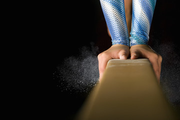 Female gymnast performing on balance beam, close-up of hands
