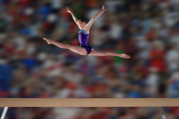 Young female (10-12) gymnast performing splits in air above balance beam, side view
