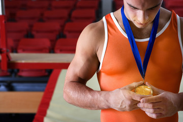Male gymnast looking at gold medal around neck, close-up