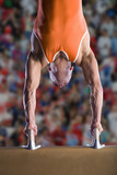 Male gymnast performing handstand on pommel horse
