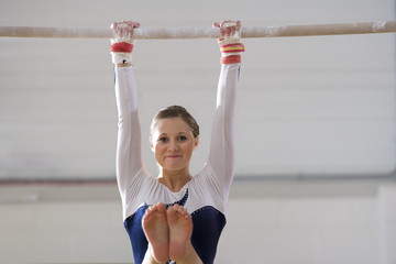 Female gymnast performing on bar, smiling, portrait