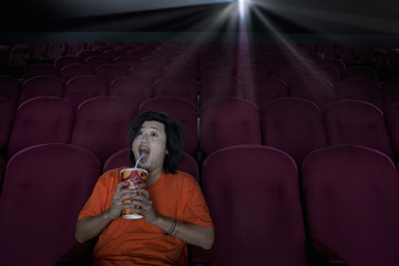 Man with drink in empty cinema making face
