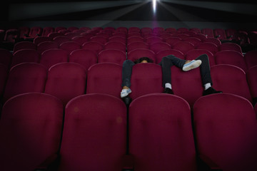 Couple in empty cinema, legs over seats, faces obscured